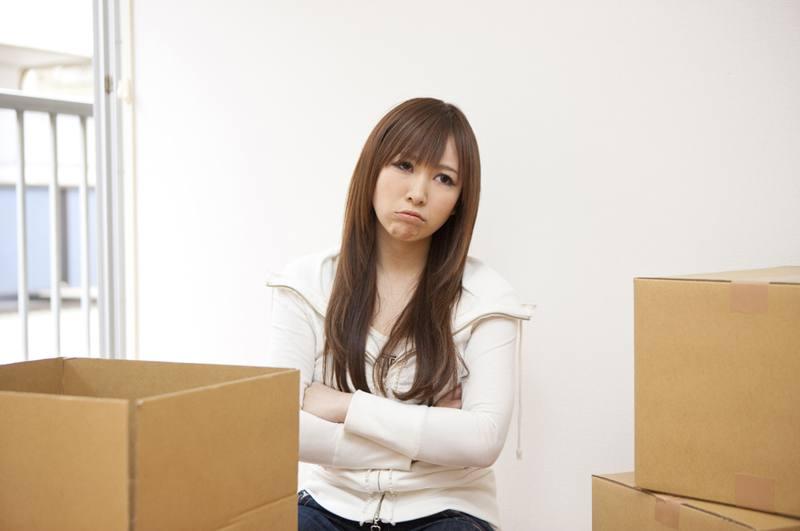 引越し梱包作業中に考え込む女性