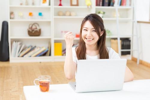 パソコンを見ながらガッツポーズをする女性