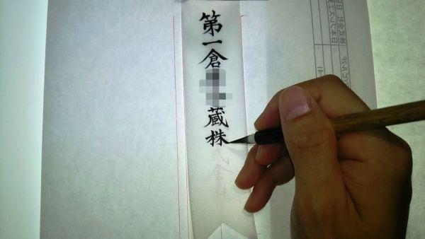 胸章リボンの筆耕は筆の穂先がリボンの繊維の溝に持っていかれます。慣れるまでコントロールが難しいのだ。