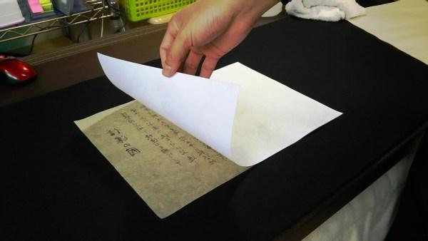 4度目の書道裏打ち作業。裏打ち用紙を乗せます。ツルツルの面がノリの面です。