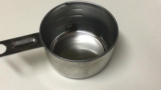 お粥づくりに計量カップを使います。