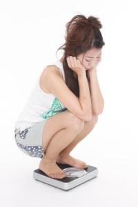 太って体重計にのる女性