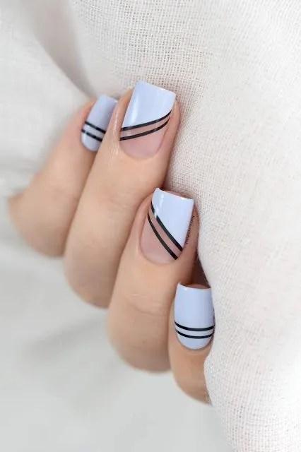 uñas postizas de color azul cielo con ralla negra y color beige