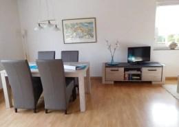 Esstisch mit vier Stühlen und Fernsehbank mit Fernseher und DVD-Player.
