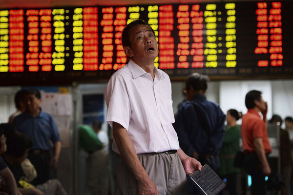 A man reacts as he looks at stock market prices at a brokerage house in Shanghai, China, Monday, June 29, 2015. Global stock markets sank Monday after Greece closed its banks and imposed capital controls in a dramatic turn in its struggle with heavy debts. the Shanghai Composite Index fell 3.3 percent to 4,053.03 despite China's surprise weekend interest rate cut. (Chinatopix via AP) CHINA OUT