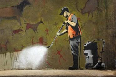 banksy-grafiti-hombre-borra-pintura-rupestre