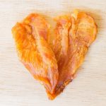 Dried chicken jerky for dogs on wooden background