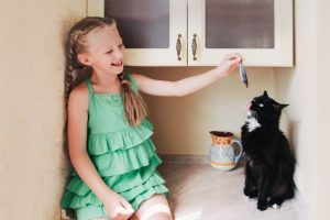 Child girl feeding a black cat in the kitchen. Black cat eating fish.