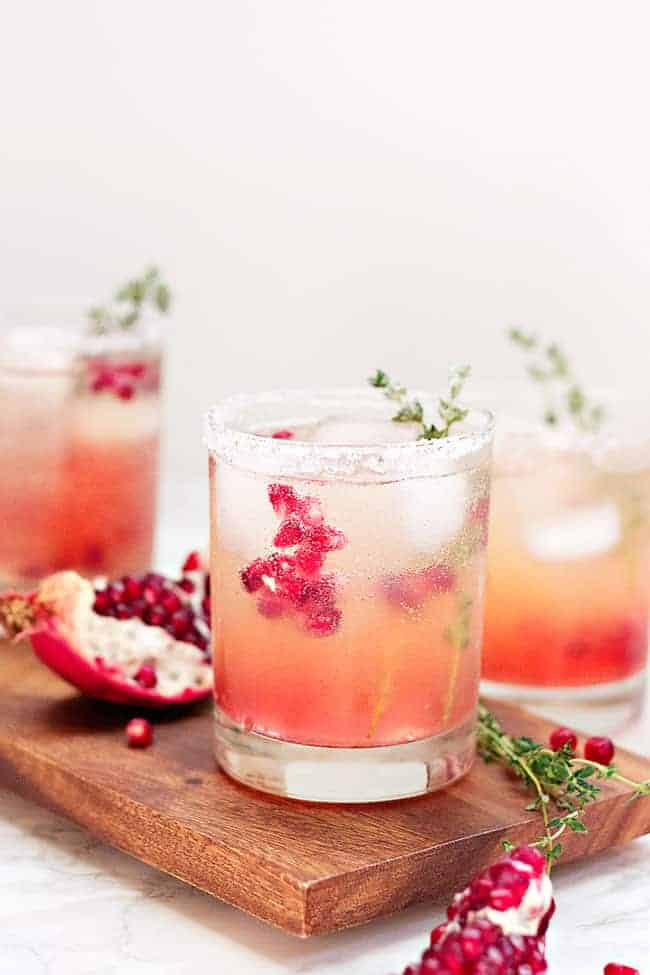 Pomegranate Pink Lemonade Punch | These Galentine's Day inspired cocktails are fun twists on classic cocktails that'll make your gal pal day festive! Choose from strawberry Moscow mules or homemade Frosé, cotton candy champagne or a pink senorita. These Galentine's day cocktails will elevate your next girls night! #xokatierosario #galentinesdaydrinks #girlsnightideas #girlsnightcocktails