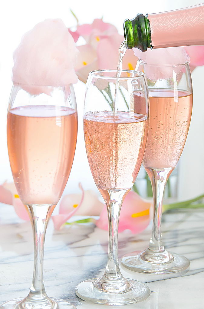 Cotton Candy Champagne Cocktail | These Galentine's Day inspired cocktails are fun twists on classic cocktails that'll make your gal pal day festive! Choose from strawberry Moscow mules or homemade Frosé, cotton candy champagne or a pink senorita. These Galentine's day cocktails will elevate your next girls night! #xokatierosario #galentinesdaydrinks #girlsnightideas #girlsnightcocktails