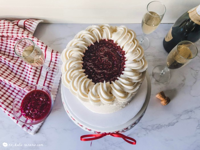 Raspberry Champagne Cake is made up of champagne infused cake with raspberry champagne jam and vanilla buttercream. Make and serve this cake to share with your girls for a fun girls night in or make it as a sweet treat for Mother's Day. The combination of champagne and raspberries is something undeniably and truly delicious. Plus, that bright red color from the raspberry jam is striking and beautiful! #xokatierosario #raspberrychampagnecake #champagnecake #homemaderaspberryjam