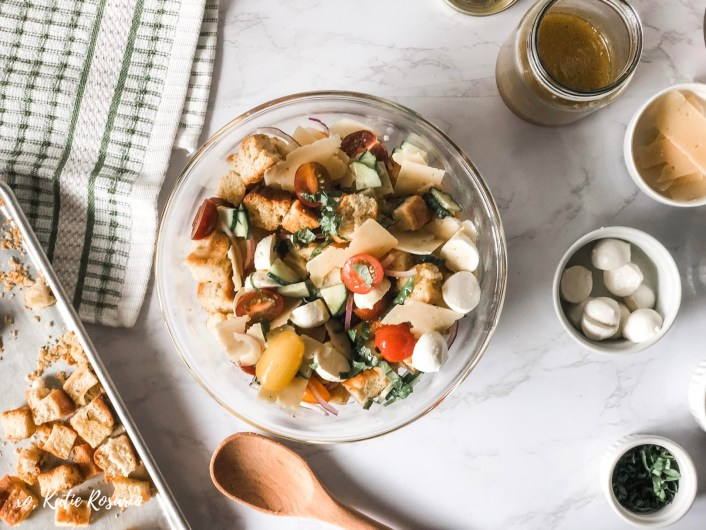 Panzanella Caprese Salad is a homemade rustic bread salad tossed with crisp vegetables, creamy mozzarella, and fresh basil. What's unique about this Panzanella Caprese salad is making focaccia bread from scratch, here is the complete recipe. It's a simple process that's really impressive. This Panzanella Caprese salad is perfect for summer entertaining. #xokatierosario #homemadebread #panzanellasalad #capresesalad #summersalad
