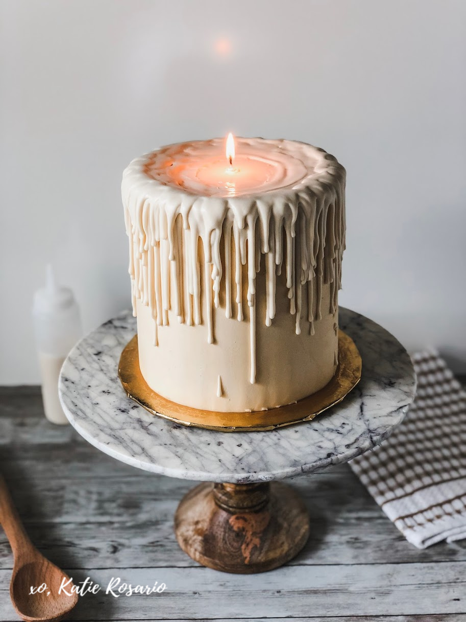 There's no better way to celebrate the holidays than with this super cute cake. This white chocolate melted candle cake has the wow factor to impress your friends and family! The real showstopper for this cake is the ivory chocolate drip; it's made with melted ivory candy melts and warm water. The many layers of white chocolate drip falling down the sides of the cake make this cake everything! #xokatierosario #meltedcandlecake #easyvanillacakerecipe #homemadevanillacake #cakedecoratingtips