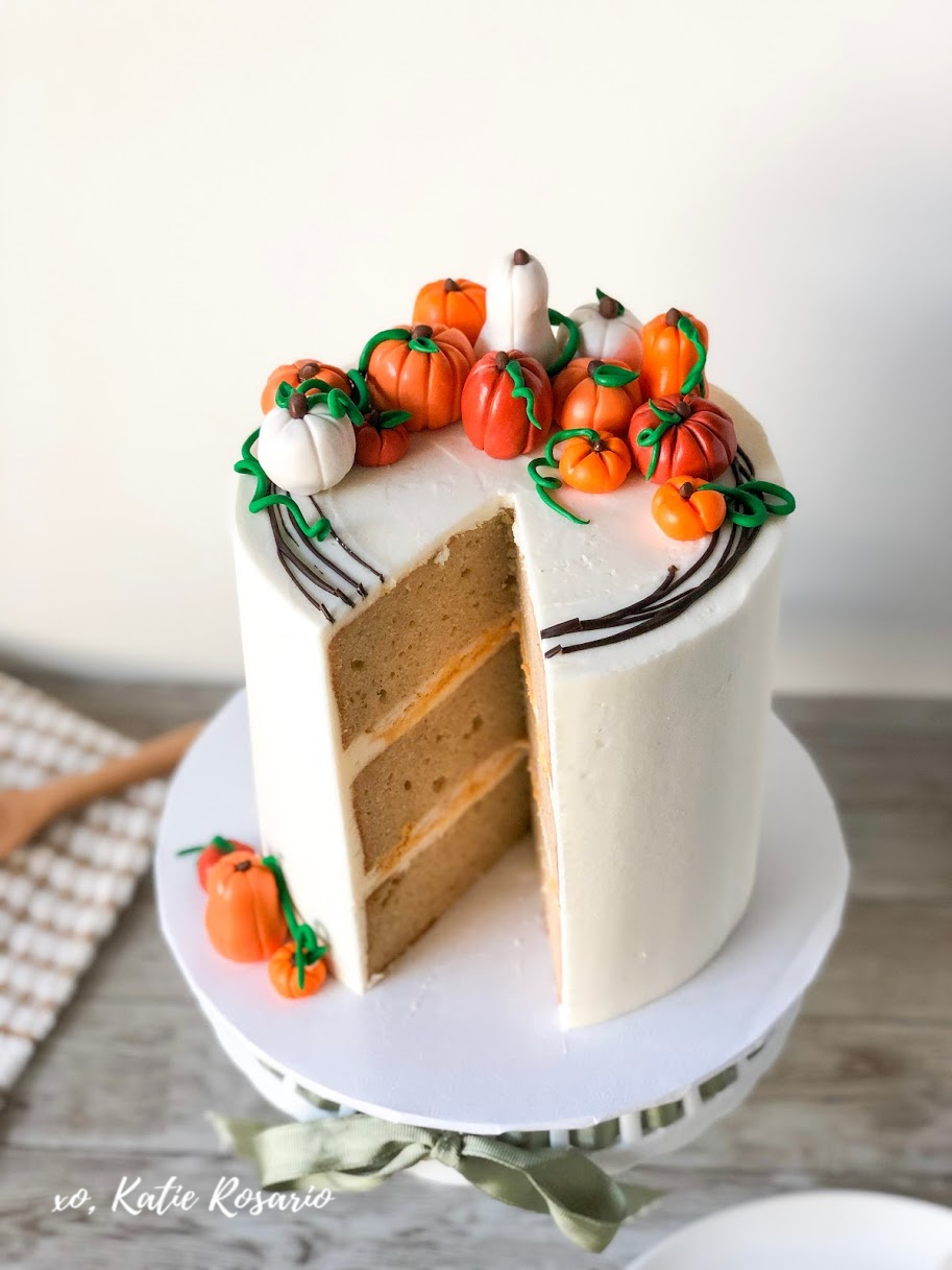 "Learn how to take your pumpkin pie ""cake"" to the next level. This Pumpkin Pie Cake is a creative spin on the traditional pumpkin pie that you're friends and family will devour! It's made with pumpkin spice cake, no-bake pumpkin cheesecake filling, buttery pie crust, and vanilla buttercream. Here's a fall-inspired cake that will have you craving a Thanksgiving pumpkin pie! #xokatierosario #pumpkinpiecake #pumpkinpatch #fallcakeideas #cakedecoratingtipsandtricks"