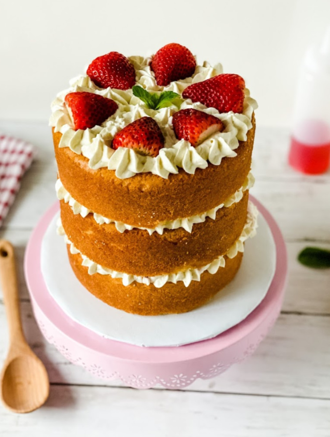 "Looking for a simple yet delicious dessert? This strawberry shortcake ""cake"" is made with fluffy vanilla cake layers, stabilized whipped cream, fresh strawberry slices, and sweet strawberry syrup. It's a freaking delicious treat that lends itself best to being turned into a cake. It makes the perfect summer dessert and easy enough for anyone to make! #xokatierosario #strawberryshortcake #strawberrycake #summerdesserts #easydessertrecipe #cakedecoratingtips"