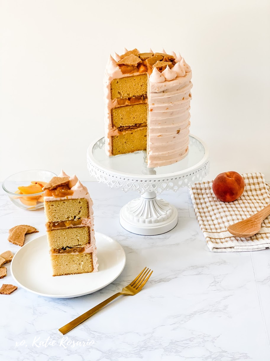 Peach cobbler is a well-loved classic dessert that is perfect for turning into a cake. This peach cobbler cake celebrates the best part of this dessert with flavorful peach filling and cobbler topping. This recipe is a modern interpretation of this beloved treat. Here's how to make this insanely delicious peach cobbler cake! #xokatierosario #peachcobbler #peachcake #summercakeideas #cakedecoratingtips