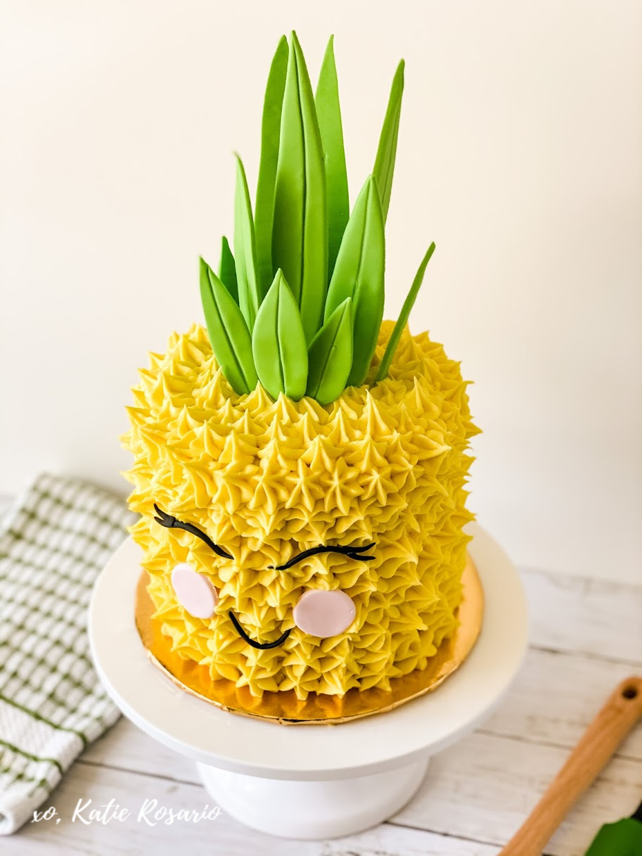 Learn how to make this adorable pineapple cake for beginner bakers! This pineapple cake is beyond cute. It's a fun characterization of a pineapple, almost like a plush toy, but it's a cake! This pineapple cake is great for many occasions like kid's birthday parties, tropical theme parties, or summer entertaining! #xokatierosario #pineapplecake #fondantpineapplecake #cakedecoratingtips #summercakeideas