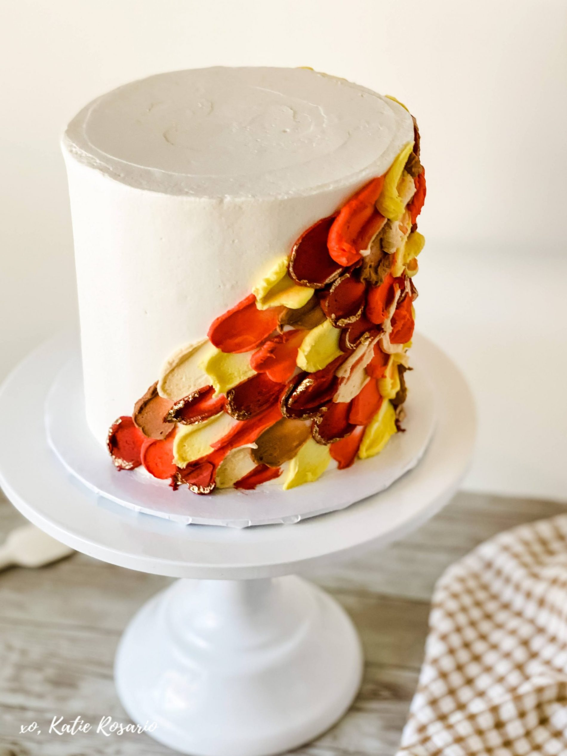 Learn how to make this insanely beautiful Autumn Painted Buttercream Cake. Painted buttercream has to be my newest cake obsession. This cake trend is so beautiful and fun to make at home. This Autumn Painted Buttercream Cake is made with light and fluffy vanilla cake layers and creamy vanilla buttercream. Here's how to make this Autumn Painted Buttercream Cake! #xokatierosario #katierosariocakes #paintedbuttercream #fallcakeideas