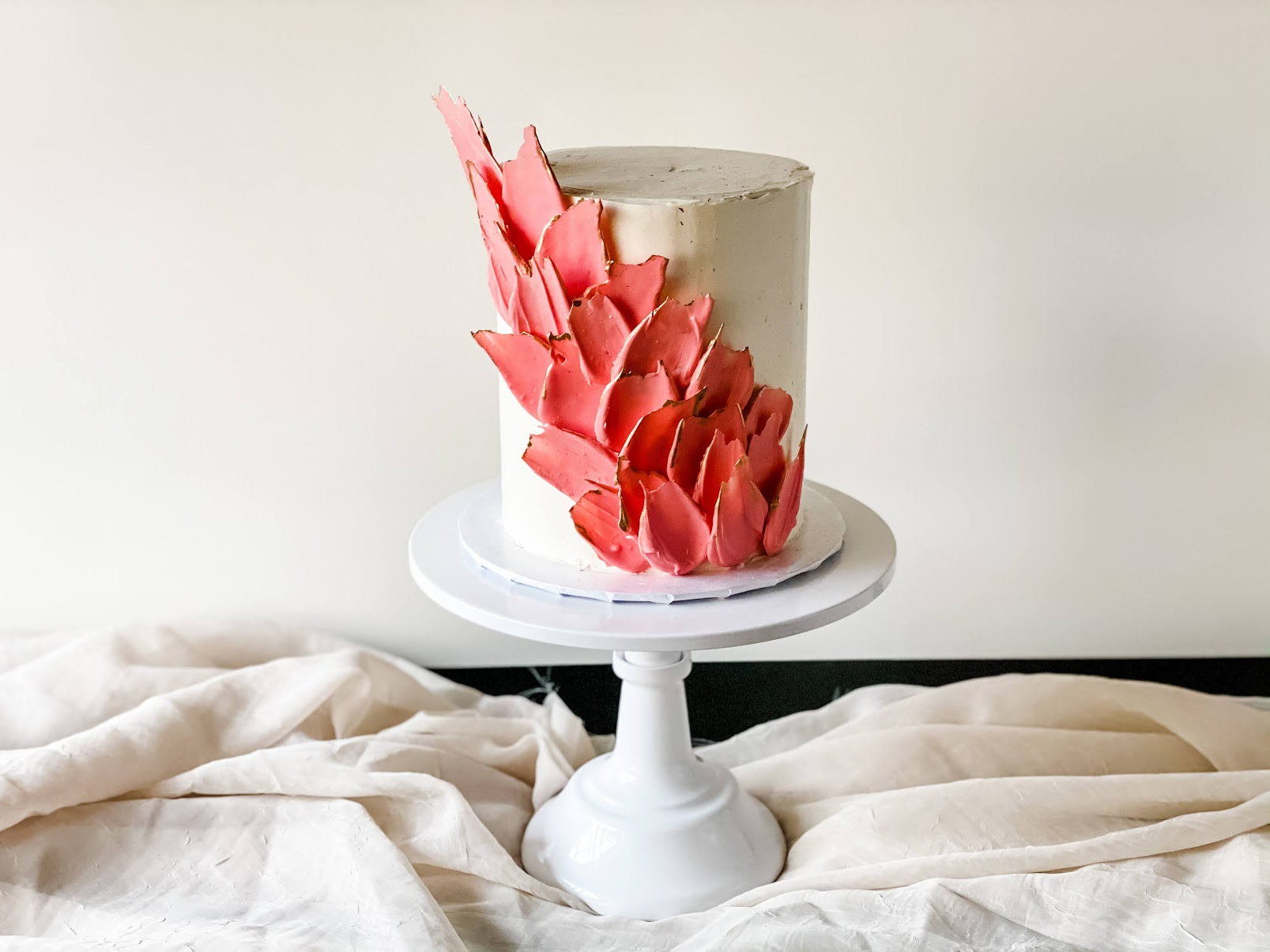 Learning how to make a wedding cake is a valuable skill. For a modern design, we are going for the clean, sleek, elegant look with white buttercream, smooth sides, flecks of edible gold, and coral-colored white chocolate feathers. #xokatierosario #katierosariocakes #smallweddingcake #modernweddingcake #chocolatefeathers #weddingcake