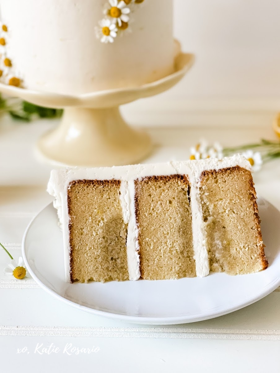 Learn how to make this Honey Chamomile Cake with XO, Katie Rosario. The best part is the delicate chamomile flowers that are perfectly placed in a modern style. This cake is sweet and delicate that's perfect for spring gatherings, Mother's Day, or even baby showers! You can Chamomile Honey Cake recipe and tutorial at XOKatieRosario.com. See you there! #xokatierosario #katierosariocakes #honeychamomilecake #honeycake #cakedecoratingtips