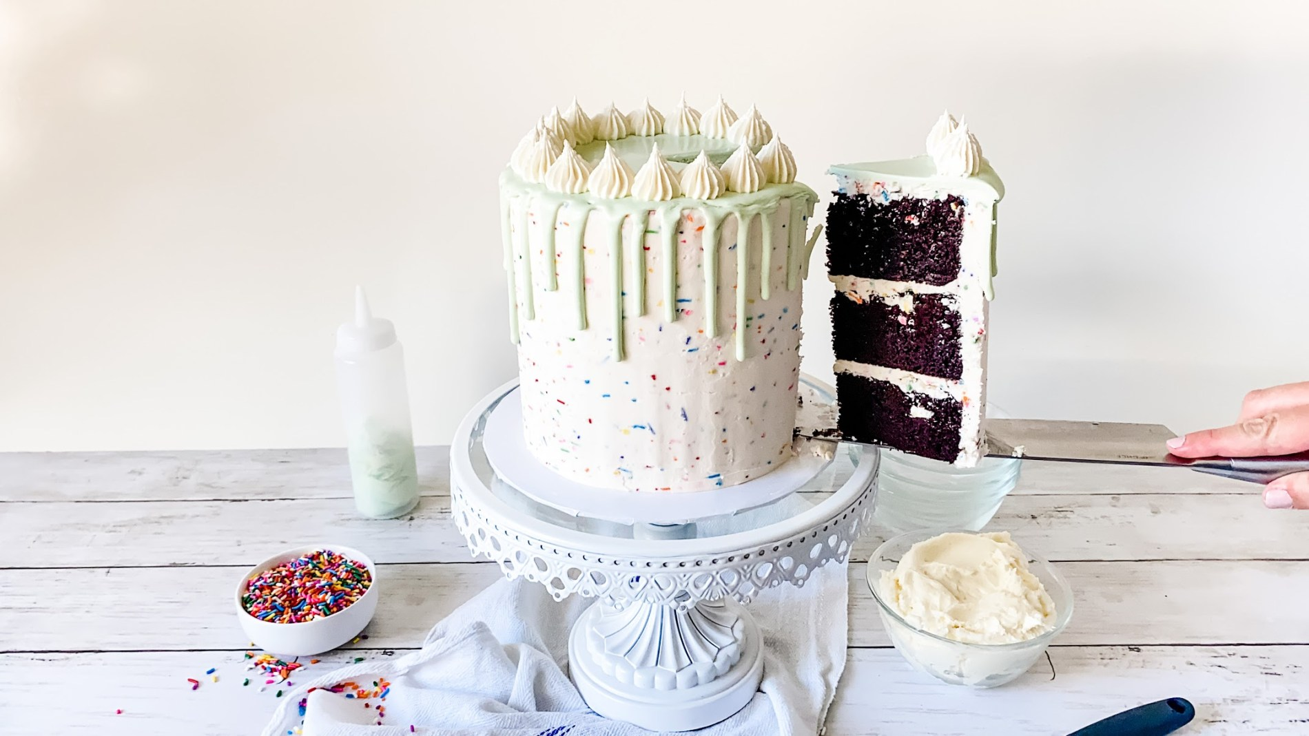 Learn how to make this simple yet sophisticated sprinkle buttercream cake! This Sprinkle Buttercream Cake is made with chocolate cake layers, filled with sprinkle vanilla buttercream and mint-colored candy dripping over the sides. Created by Katie Rosario, XOKatieRosario creates beautiful cake decorating techniques that are easy for beginners and strategically designed for any home baker. #xokatierosario #katierosariocake #cakedecorating #sprinkles #easybuttercream #cakedecoratingcourse