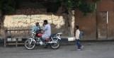 Man on bench, bike and boy