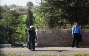 Man in Gjebella & man in suit wait on corner in Luxor