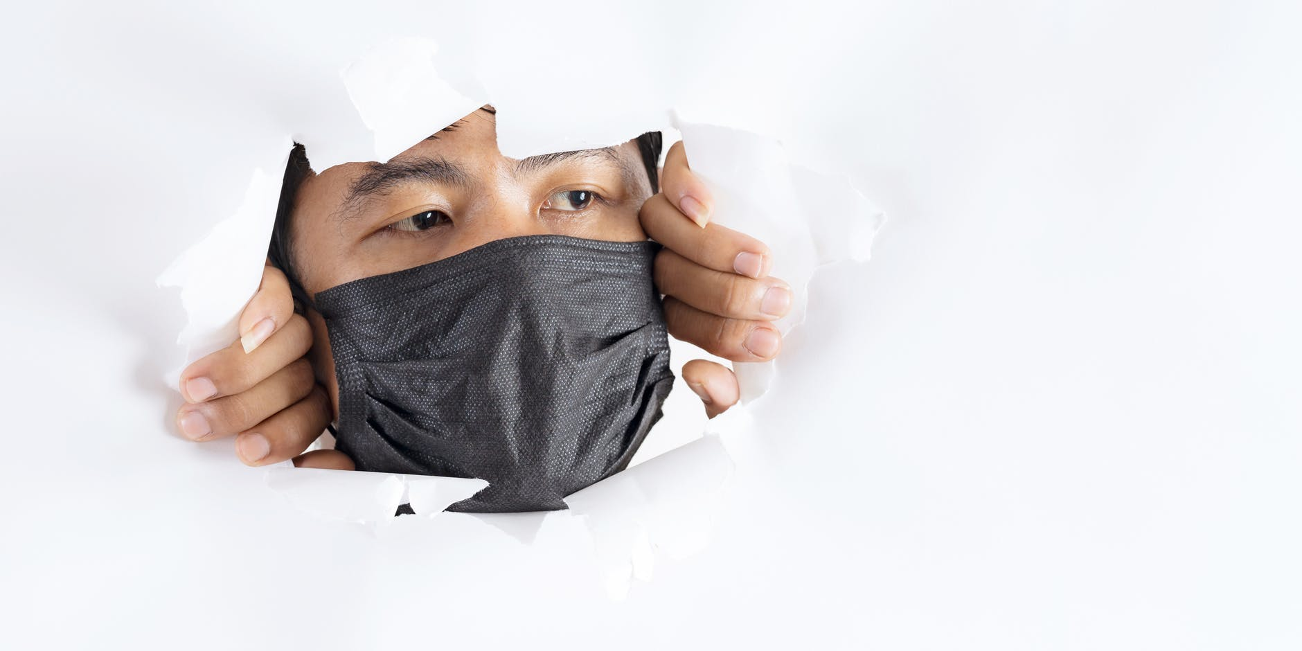 crop attentive man in face mask behind torn paper wall