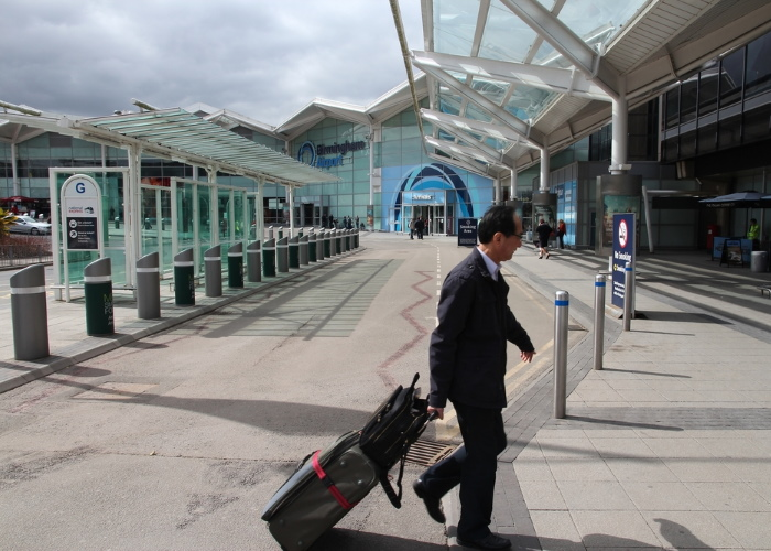 Man carrying suitcase into Birmingham Airport