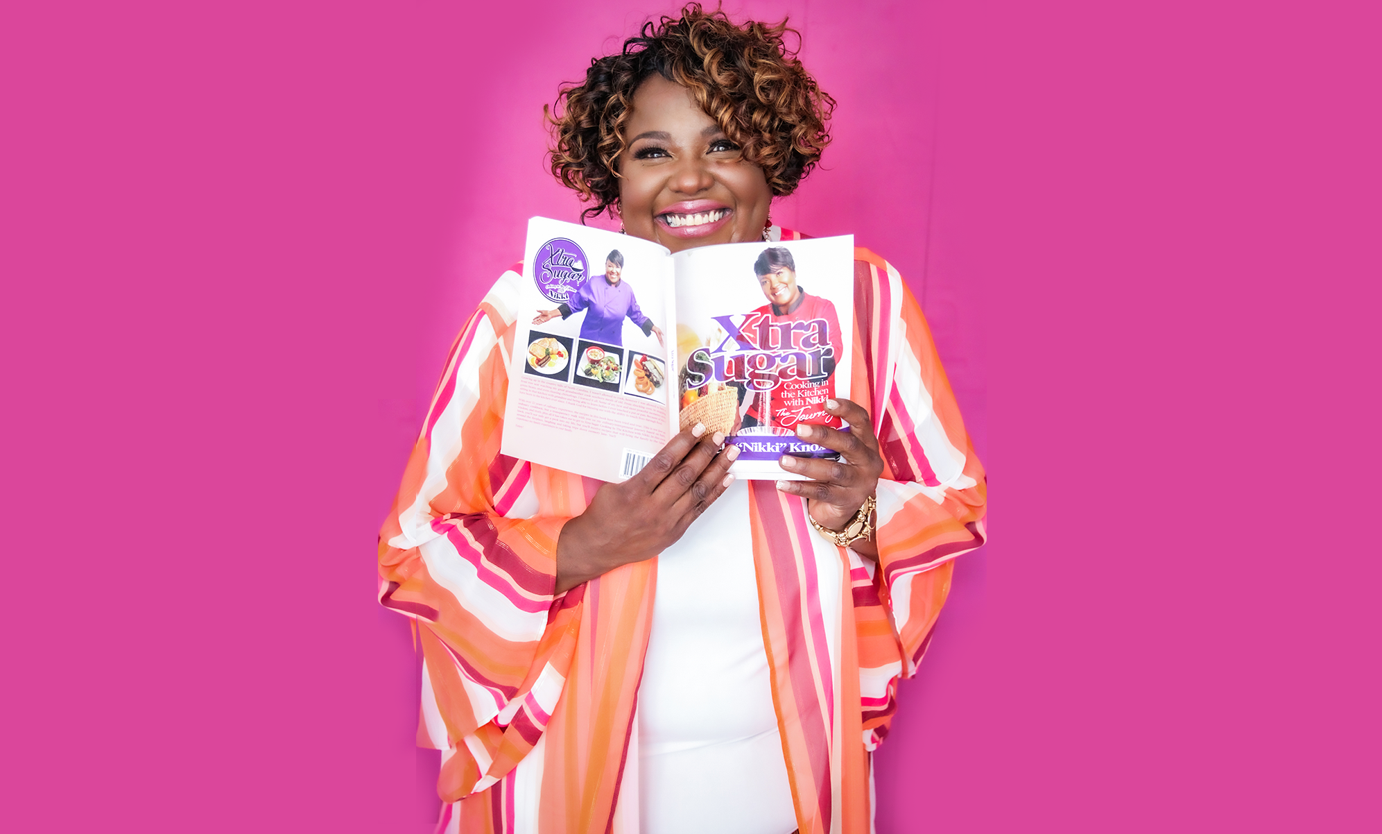 Chef Nikki on a hot pink background holding an opened version of the XtraSugar cookbook