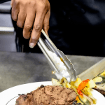 Chef Nikki's hands holding metal tongs placing veggies on a plate with a steak