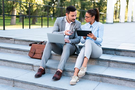 Young handsome businessman and businesswoman sitting together outside on the stairs discussing business plans using laptop and tablet