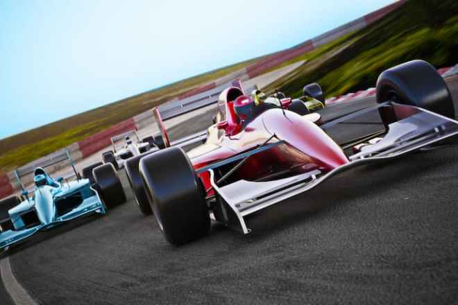 Three Formula 1 cars race rounda track