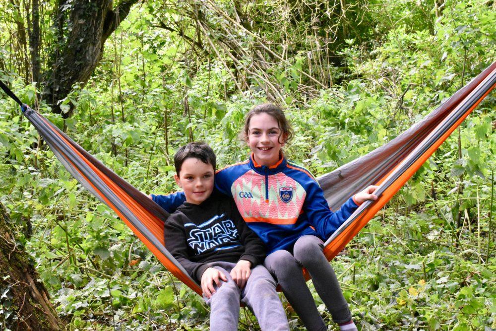 Two kids enjoying the hammocks at Base Camp of Xtreme.ie's Bushcraft Birthday Parties.