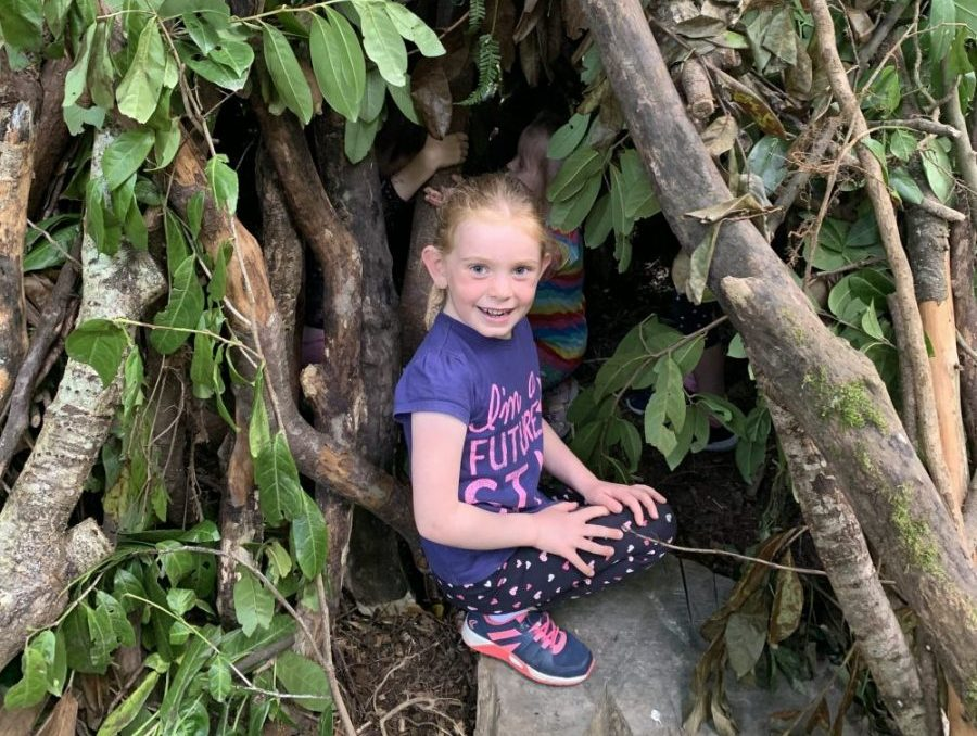A child sitting in the shelter she built during her Bushcraft Birthday Party at Carton House hosted by Xtreme.ie.