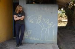 Jeppe naast de voormalige kleuterschool achter in onze tuin met zijn kindertekening nog op de muur