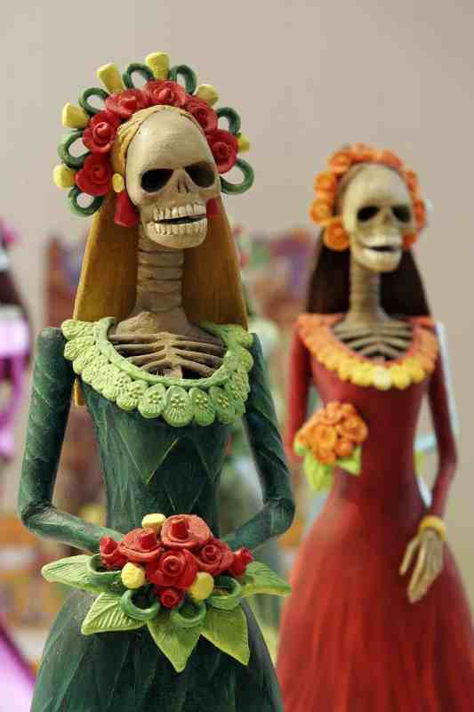 catrinas in papier mache calaveras dressed for celebrations