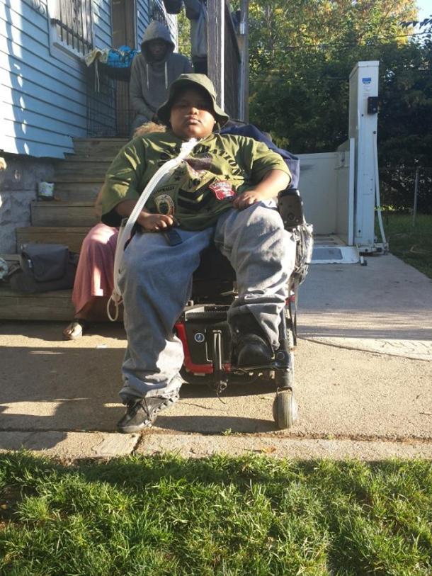 Xzavier Davis-Bilbo in front of his wheelchair lift