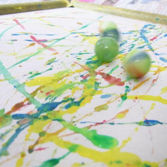 絵の具の付いたビー玉が紙の上を転がっている画像