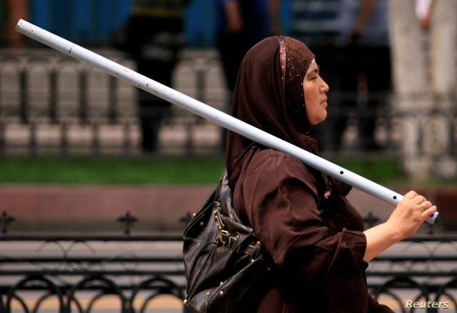 FILE PHOTO: An ethnic Uighur woman carries a metal rod as she walks down a main road in the city of Urumqi in China's Xinjiang Autonomous Region