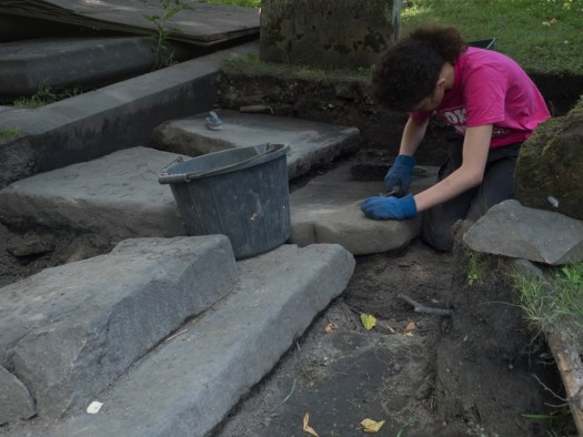 Erin carefully scrapes the compacted mud from one of the prettier stones