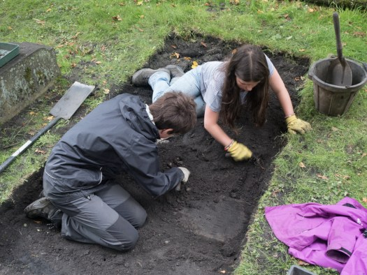 Olivia and Alexander clearing another gravestone