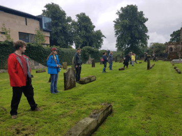 The 2019 field school students line up to conduct a pedestrian survey of the graveyard stone types.