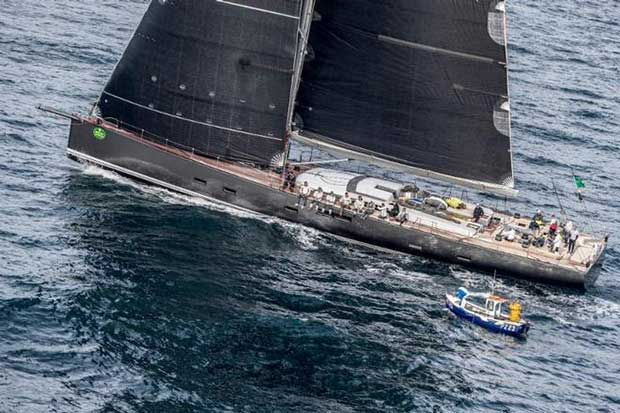 At 115ft, Nikata the largest boat in the Rolex Fastnet Race passes a very small fishing boat en route back from the Rock © Rolex/ Kurt Arrigo http://www.regattanews.com
