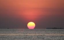 Setting sun spilling over horizon