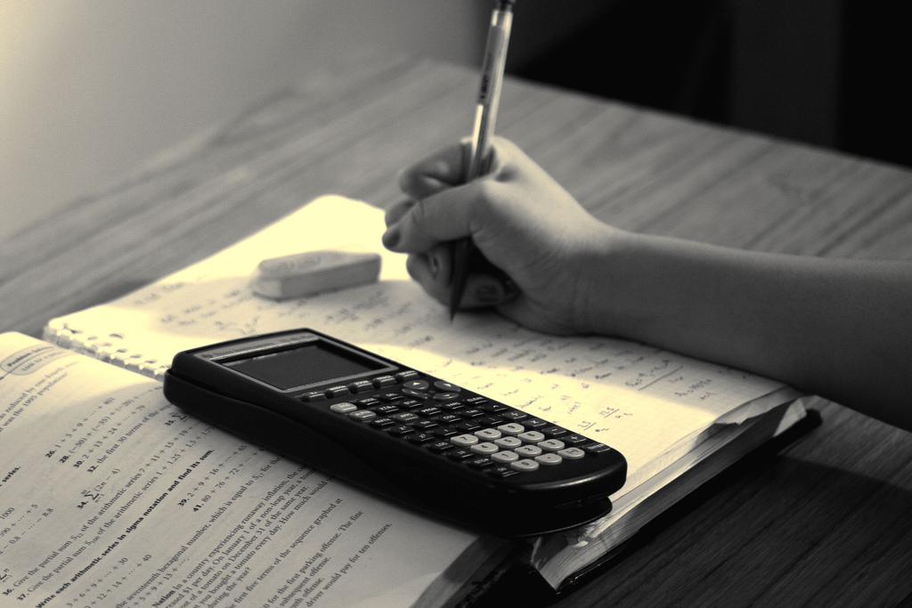 Photograph of textbook, calculator and a person writing in a notebook