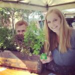 NUSEC members at their stall with a planter box of herbs