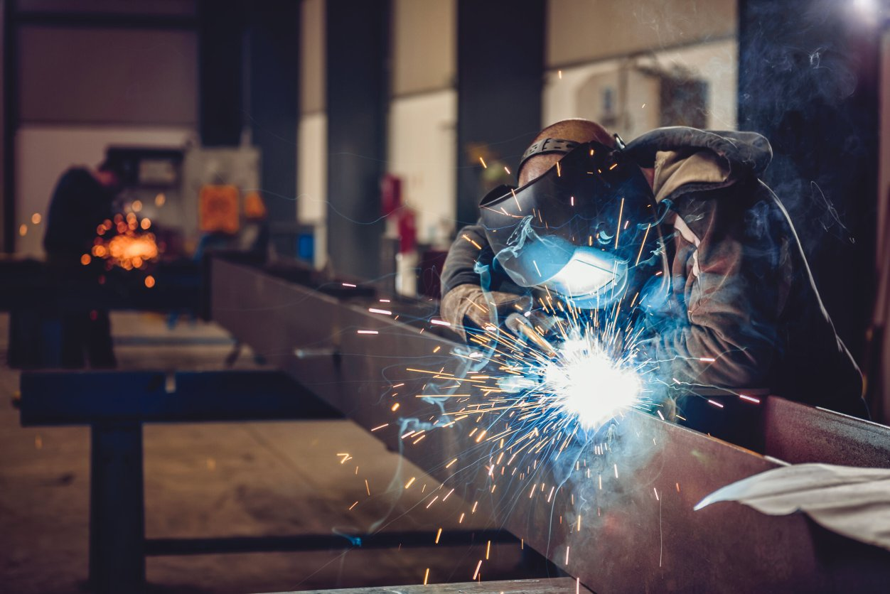 Industrial,Welder,With,Torch,And,Protective,Helmet,In,Big,Hall