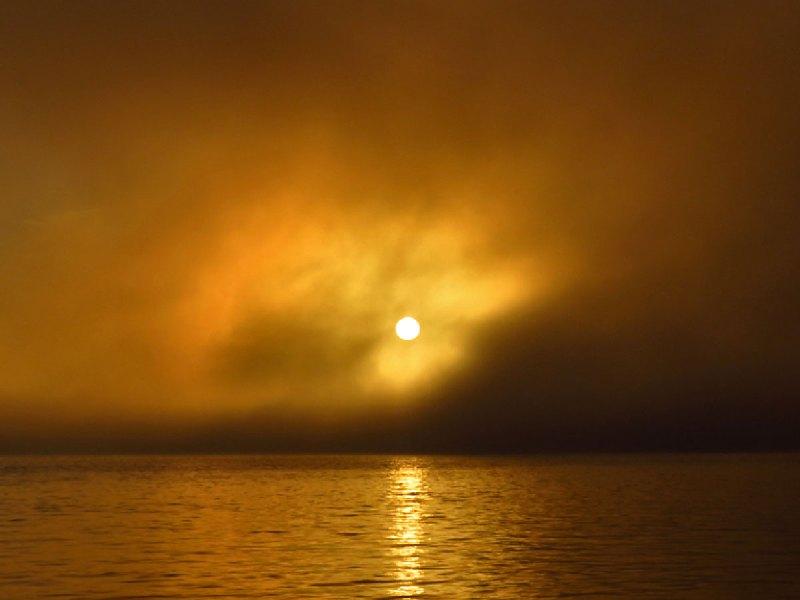 The sun sets through mist over a river.