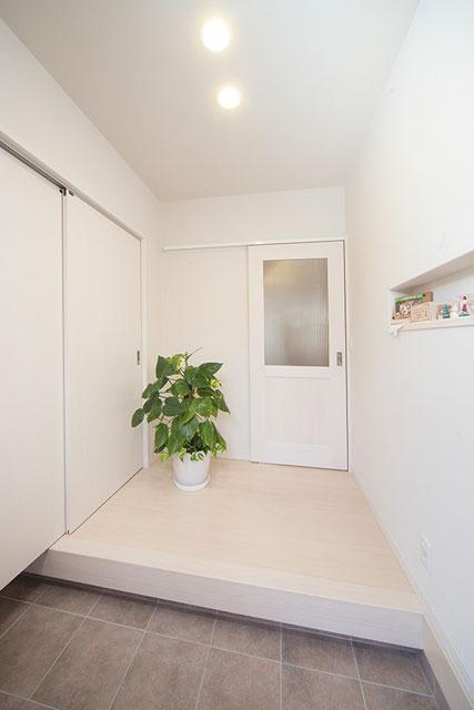 真っ白でシンプルな玄関。シューズクロークを設置しているので、家族全員の靴やベビーカーもすっきり収納。
